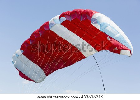 Red parachute on a blue sky. - stock photo