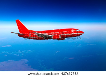 Red passenger airplane is flying high in the deep-blue sky - stock photo