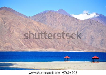Red pavilions with blue lake and snow mountain in background and clear blue sky at Pangong Lake, India - stock photo