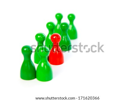 Red pawn in a line-up of green pawns against white background - stock photo