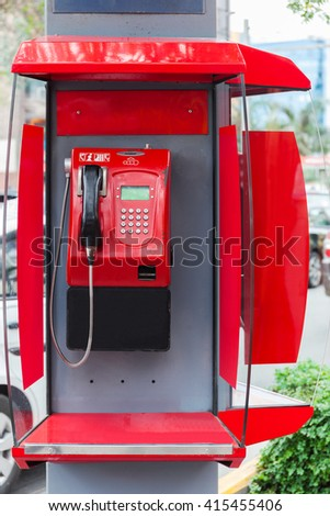 red payphone on a city street - stock photo