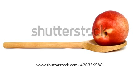 red peach on wooden spoon isolated on white