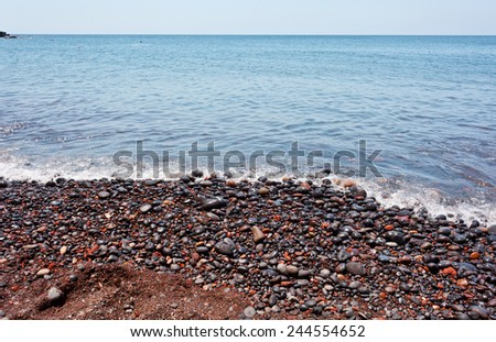 Red pebbles of the typical red beach of Santorini, Greece.