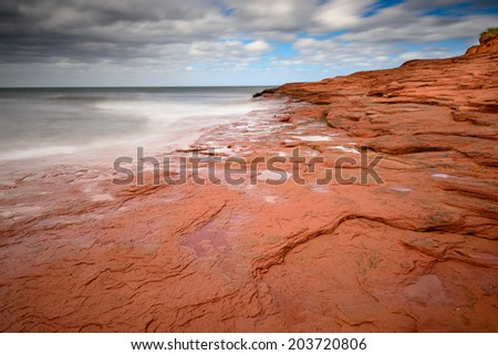 Red PEI Sandstone in waves as hurricane approaches - stock photo