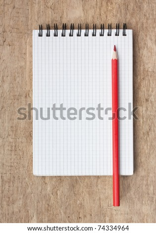red pencils and notebook on a wooden background