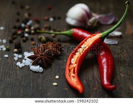red pepper and spices on wooden background - stock photo