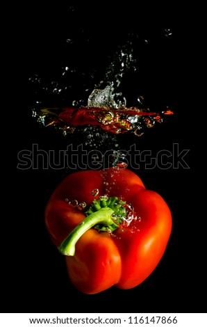 red pepper falls in the water before black background - stock photo
