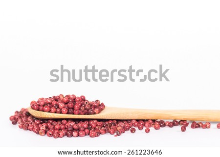 red peppercorns in wooden spoon. isolated on white background.