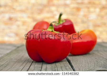 Red peppers on old wooden table - stock photo