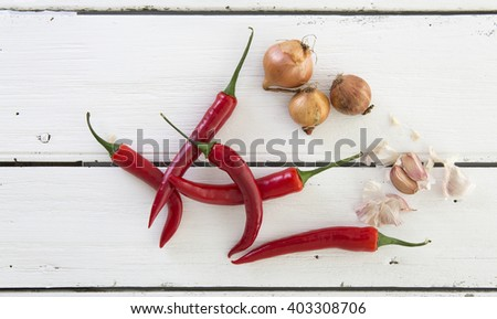 Red Peppers with Garlic and Shallots on a rustic white wooden table - stock photo
