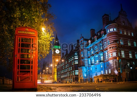 Red phone booth is one of the most famous of London icons at night - stock photo