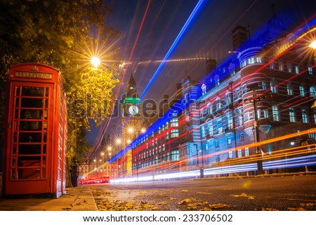Red phone booth is one of the most famous of London icons with bus blur at night - stock photo