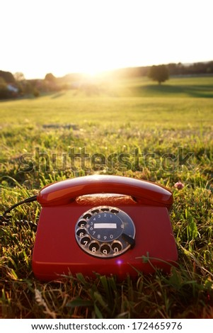 red phone in landscape - stock photo
