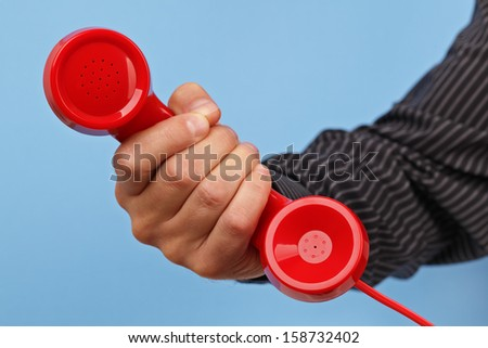 Red phone over blue background concept for customer support line or important call - stock photo