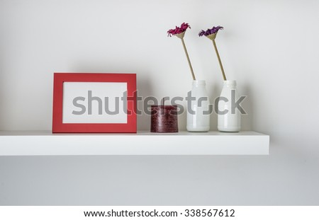 Red photo frame on a minimal white wall shelf - stock photo