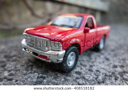 Red pick up truck toy on the road. Shallow depth of field - stock photo