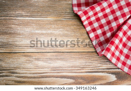 Red picnic cloth on wooden background.Napkin tablecloth on old wood with empty space for text. - stock photo