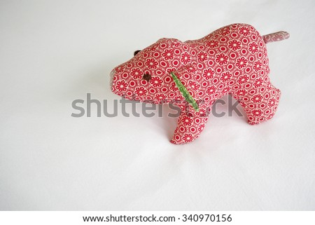 Red pig doll on white background. Toned image. - stock photo