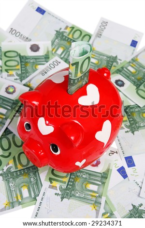 Red piggy bank on heaps of euros - stock photo
