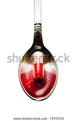 Red pill on spoon isolated with clipping path