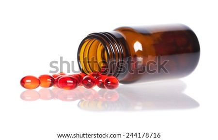 Red pills an pill bottle, isolated on white background - stock photo