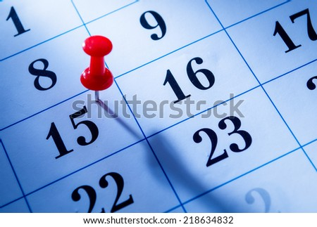 Red pin marking the 15th on a calendar as a reminder of an important event, close up low angle view - stock photo