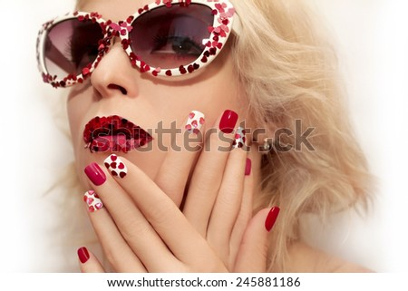 Red pink manicure and makeup with hearts on the blonde girl with glasses.