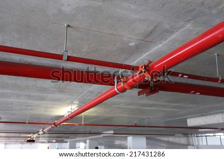 red pipeline extinguishing water in industrial building - stock photo