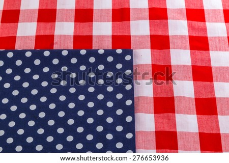 Red Plaid Tablecloth with blue and white polka dot napkin to symbolize American Flag on Fourth of July Picnic. - stock photo