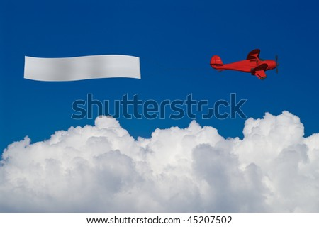 Red plane pulls blank banner over white clouds - stock photo