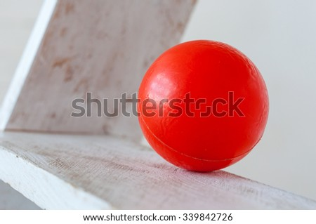 Red plastic ball on white ledders step background. - stock photo