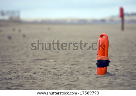 Red plastic buoyancy aid in the sand on lonely beach - stock photo