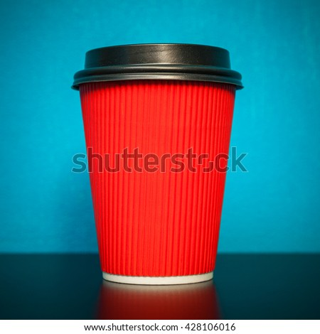 red plastic cup on a turquoise background - stock photo