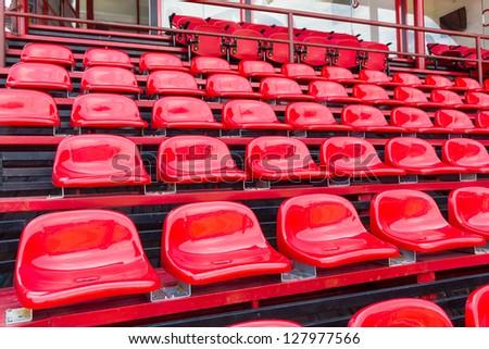 Red plastic seats in stadium for sport - stock photo