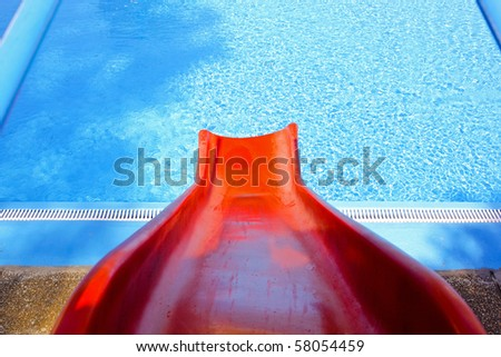 Red plastic slider in front of swimming pool - stock photo