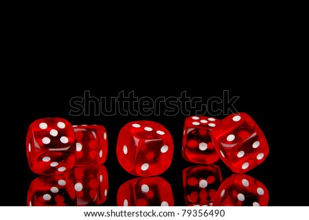 Red playing dices isolated on black background - stock photo