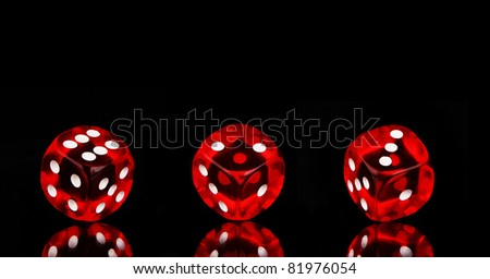 Red playing dices isolated on black background