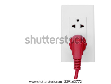 Red plug in a socket / Energy consumption concept - stock photo