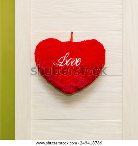 Red plush heart on wood wall - stock photo