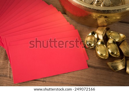 Red pocket and ancient Chinese golden ingots on wooden : with copyspace - stock photo