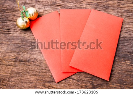 Red pockets and golden oranges on wooden table - stock photo