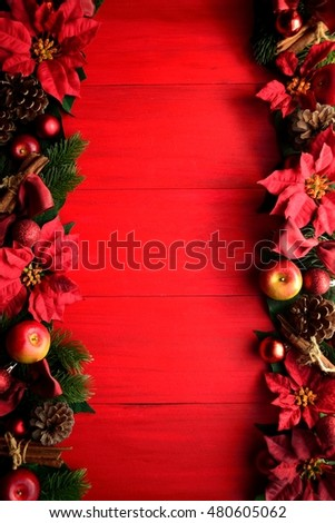 Red poinsettia with Christmas ornaments on red wooden background