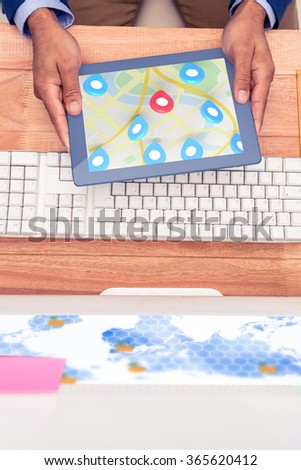 Red pointer surrounded by blue markers on world map against businessman holding digital tablet by keyboard at desk