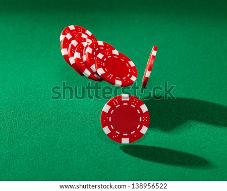 Red poker chips closeup on green cloth