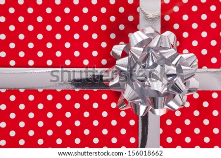 Red polka dot gift paper with silver bow and ribbon. - stock photo