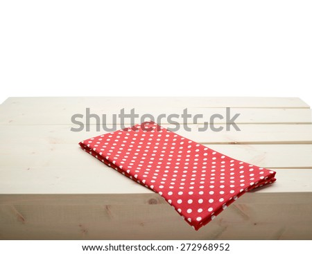 Red polka dot tablecloth or towel over the surface of a wooden table, composition isolated against the white background - stock photo