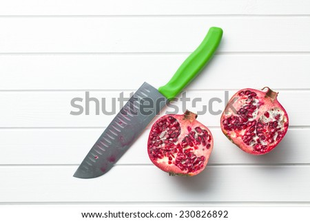 red pomegranate on kitchen table - stock photo