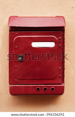 Red postbox mounted on wall with whiteboard for text - stock photo