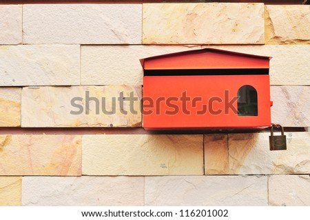 Red Postbox on wall of Sandstone - stock photo