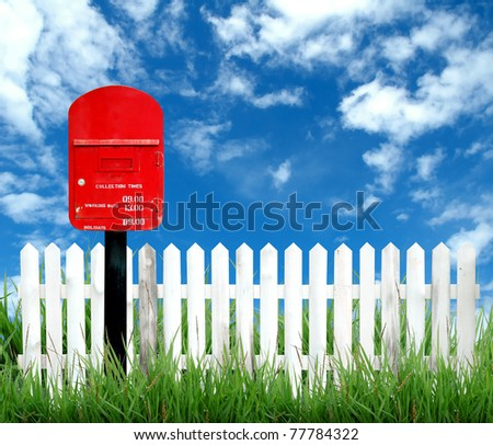 red postbox with white fence and blue sky - stock photo
